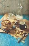 Galleta con los cacahuetes y la formación de hielo del chocolate, taza azul de leche Fotografía de archivo