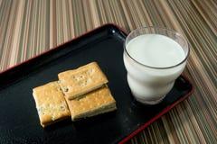 Galleta con un vidrio de leche en la placa Imagen de archivo libre de regalías