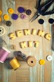 Galleta de ABC y herramientas de costura en fondo de madera del vintage Foto de archivo