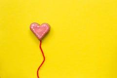 Galleta de azúcar en forma de corazón en fondo amarillo Concepto de la tarjeta del día de tarjetas del día de San Valentín Fotos de archivo