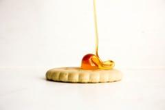 Galleta de la galleta un descenso redondo de la miel pegajosa encima de la colada Imagen de archivo libre de regalías