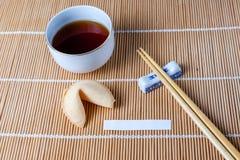 Galleta de la suerte con resbalón y palillos y té Foto de archivo