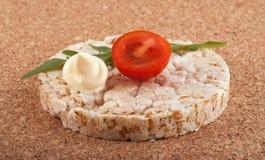 Galleta del arroz con el tomate en una tabla del corcho fotos de archivo libres de regalías
