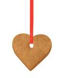 Galleta del corazón de la Navidad en la cinta roja aislada en blanco Fotografía de archivo libre de regalías
