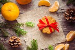 Galleta del pan de jengibre con los mandarines en fondo de la Navidad Imagen de archivo