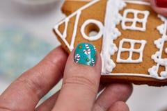 Galleta del pan de jengibre de la Navidad en mano femenina Fotos de archivo libres de regalías