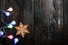 Galleta del pan de jengibre de la Navidad y guirnalda colorida en la parte posterior de madera Foto de archivo