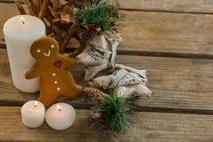 Galleta del pan de jengibre de la opinión de alto ángulo con el adornamiento de la forma de la estrella y velas iluminadas Fotos de archivo libres de regalías