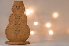 Galleta del pan de jengibre del muñeco de nieve con las luces de la Navidad Foto de archivo libre de regalías