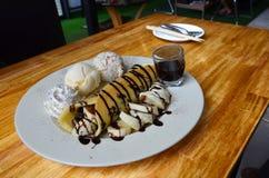 Galleta del plátano con helado y el desmoche del chocolate Foto de archivo libre de regalías