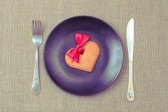 Galleta en forma de corazón del pan de jengibre en la placa negra imagenes de archivo