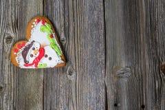 Galleta en forma de corazón del pan de jengibre de la Navidad en la tabla de madera Imagen de archivo libre de regalías