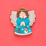 Galleta hecha en casa del ángel del pan de jengibre de la Navidad en fondo rojo Fotos de archivo