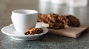Galleta hecha a mano del cereal con la taza del café con leche en una tabla de cortar de madera Imagen de archivo libre de regalías