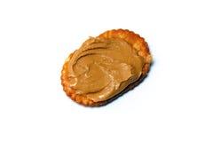 Galleta oval con mantequilla de cacahuete sobre blanco Foto de archivo