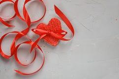 Galleta roja de la forma del corazón con la cinta en fondo de piedra gris El día de tarjeta del día de San Valentín y romántico imagen de archivo
