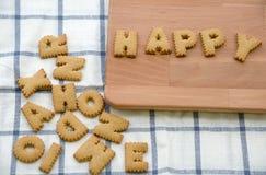Galletas ABC bajo la forma de alfabeto FELIZ de la palabra en fondo de madera Imagen de archivo