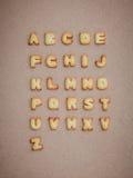 Galletas ABC bajo la forma de A-Z del alfabeto en backg marrón de la cartulina Fotografía de archivo libre de regalías