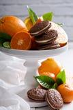 Galletas anaranjadas del chocolate con el relleno poner crema Imagen de archivo