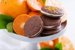 Galletas anaranjadas del chocolate con el relleno poner crema Foto de archivo libre de regalías