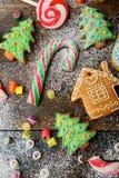 Galletas, bastón, piruleta y caramelo del jengibre de la Navidad derramados con nieve Imagen de archivo