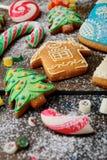 Galletas, bastón y caramelo de Ginger Christmas derramados con nieve Imagen de archivo libre de regalías