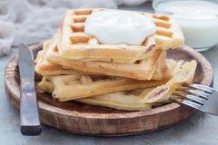 Galletas belgas sabrosas hechas en casa con el tocino y el queso destrozado, servidos con el yogur llano en la placa de madera, h Fotos de archivo libres de regalías