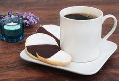 Galletas blancos y negros con una taza de café Fotos de archivo libres de regalías