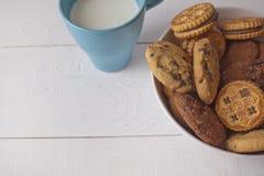 Galletas clasificadas en cuenco con leche de la taza Foto de archivo libre de regalías