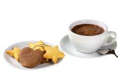 Galletas clasificadas en la placa de postre y la taza blancas de chocolate caliente Fotos de archivo libres de regalías