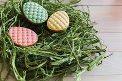 Galletas coloridas de los huevos de Pascua en jerarquía en fondo de madera ligero foto de archivo