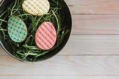 Galletas coloridas de los huevos de Pascua en jerarquía en fondo de madera ligero foto de archivo libre de regalías