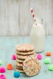 Galletas coloridas del confeti apiladas con leche y bolas decorativas Foto de archivo