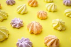 Galletas coloridas del merengue en fondo amarillo imágenes de archivo libres de regalías