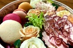 Galletas coloridas deliciosas de los macarrones en una caja de regalo junto con el ramo floreciente de rosas, mattiola, claveles  imágenes de archivo libres de regalías