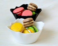 Galletas coloridas dulces de los macarrones en cuencos blancos y negros Fotografía de archivo