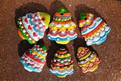 Galletas coloridas en un fondo marrón, galletas de los árboles de navidad de la Navidad adornadas para los niños Foto de archivo libre de regalías