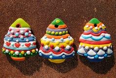 Galletas coloridas en un fondo marrón, galletas de los árboles de navidad de la Navidad adornadas para los niños Fotografía de archivo