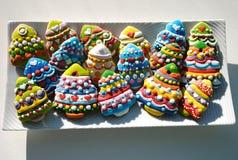 Galletas coloridas en una placa blanca, galletas de los árboles de navidad de la Navidad adornadas para los niños Foto de archivo
