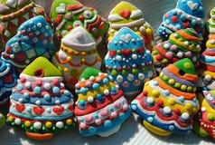 Galletas coloridas en una placa blanca, galletas de los árboles de navidad de la Navidad adornadas para los niños Imagen de archivo