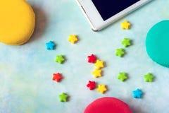 Galletas coloridas hechas en casa y pantalla en blanco en el teléfono elegante, concepto de los macarrones del día de tarjetas de Fotos de archivo