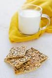 Galletas con cereales y una taza de leche en una tabla de madera blanca fotografía de archivo