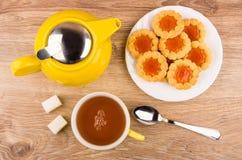 Galletas con el atasco en la placa, tetera, taza de té, azúcar Fotografía de archivo