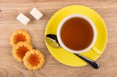 Galletas con el atasco, la taza de té, el azúcar y la cuchara Imagen de archivo