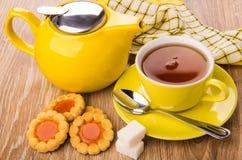 Galletas con el atasco, la tetera, la taza de té, el azúcar y la cuchara Imágenes de archivo libres de regalías