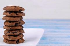 Galletas con el chocolate doblado en una pila en una servilleta blanca en una tabla de madera azul bake delicioso Espacio para el fotografía de archivo libre de regalías