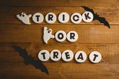 Galletas con el texto del truco o de la invitación por las decoraciones fantasmagóricas en la tabla Imagen de archivo