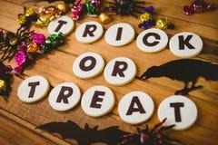 Galletas con el texto del truco o de la invitación por las decoraciones y los chocolates en la tabla Fotografía de archivo libre de regalías