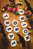 Galletas con el texto del truco o de la invitación por los chocolates y las decoraciones en la tabla Fotos de archivo libres de regalías