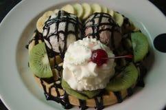 Galletas con helado de vainilla y plátano y crema azotada Foto de archivo
